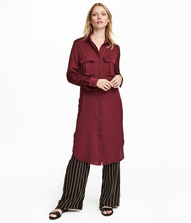 Burgundy. Knee-length satin shirt dress with a collar. Buttons at front, chest pockets with flap, tie belt at waist, and rounded hem with slits at sides.