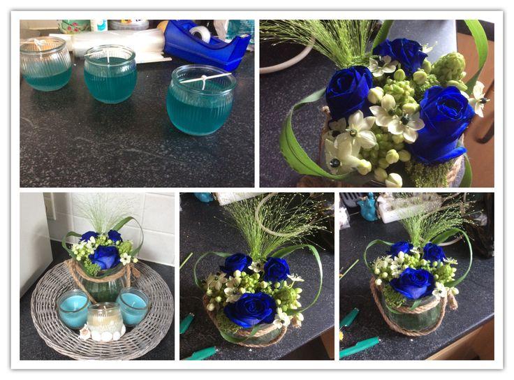 Bloemstuk blauwe rozen en zelfgemaakte kaarsen