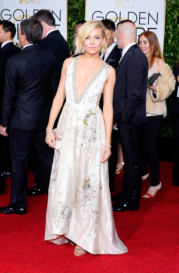 Sienna Miller wearing a Miu Miu ivory silk duchesse gown with sheer tulle back, Tiffany & Co. jewelry, and Jimmy Choo sandals at the 72nd Annual Golden Globes