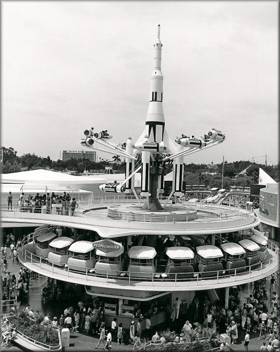 Guests line up to board the PeopleMover on the loading deck at the Rocket Jets in Tomorrowland.