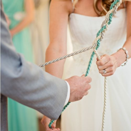 """Instead of lighting the traditional unity candle during the ceremony, the couple opted to do a God's Knot, tied with the light mint green and ivory color themes of the day. The """"knot"""" consisted of three strands, one to represent Cristin, one for Mike, and one for God - the meaning behind was that the couple ties their life in together and with God."""