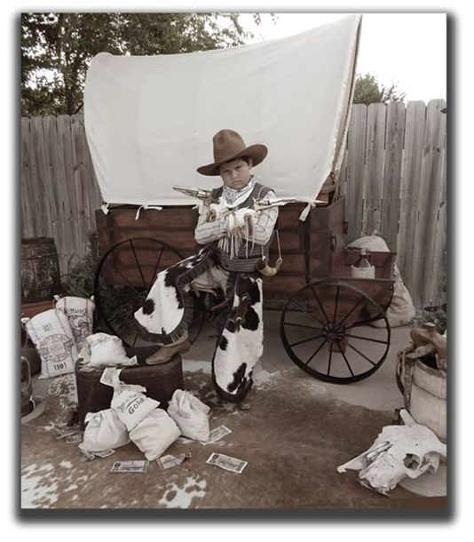"""""""You Callin' Me A Cheat?"""" Old Time Photo Booth for rent in Little Rock AR with complete mobile service to the entire USA, complete with Wagon Backdrop, Costumes, Chaps, Money Bags, Chinks, Accessories, Pistols, & Guns!"""