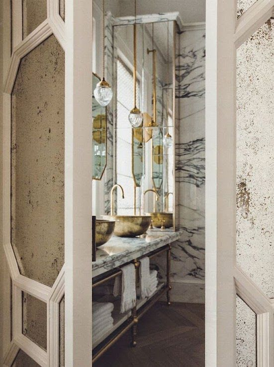 Antiqued Mirrored Bi Fold Doors Open To Exquisite Bathroom