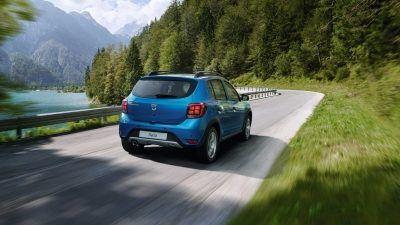 Dacia Sandero Stepway - vůz jedoucí na silnici podél lesa