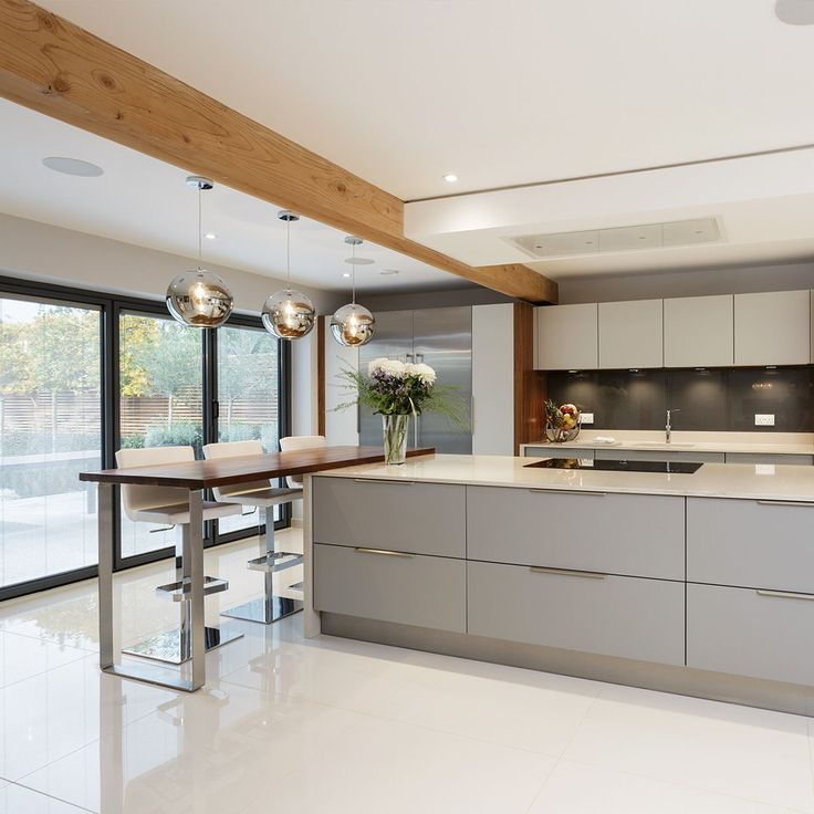 Modern open plan kitchen with bi-fold doors. White…