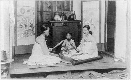 Korean woman ironing with wooden sticks circa 1910.
