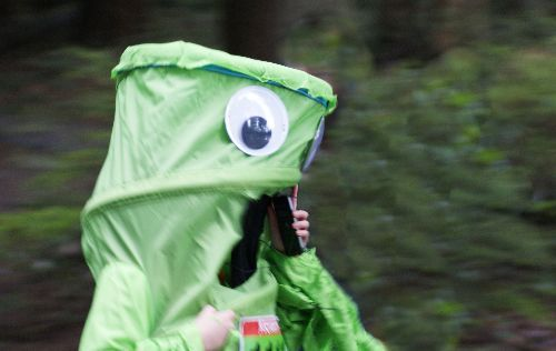 A funny green creature talking on the phone while running in the St. Patrick's Day 5K Run in Vancouver's Stanley Park