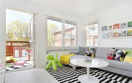 12 White Rooms with Pops of Color: The ubiquitous black and white IKEA rug in offset stripes is a sure bet on a white floor. The plain pale gray sofa is enlivened by plush toys and pillows, and a ledge filled with art above may just be for kids' creations. Photo via StyleRoom, a Swedish scrapbook site.