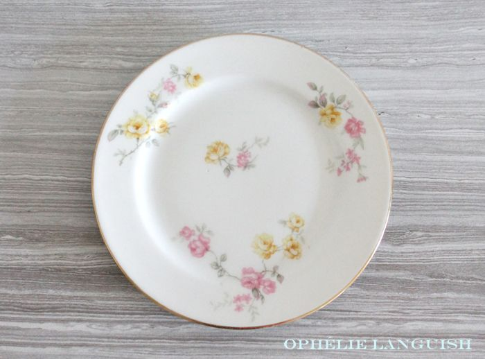 Set of two shabby chic side/bread/dessert plates in variations of the same pattern. Pattern features a pink and yellow rose sprig motif with gold trim. Classically elegant.