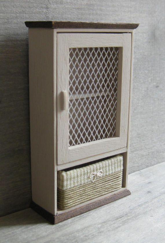 Este armario incluye una cesta de almacenamiento extraíble con una tela verde y crema comprobada. Tiene una puerta de malla y un estante interno. El armario de la pared se ha pintado con una pintura de crema oscuro y tiene una tapa barnizada roble. Esta unidad tendría una hermosa adición a cualquier habitación de casa de tus muñecas. Medidas: 90mm (3 1/2 pulgadas) de alto x 52mm (2 1/16 pulgadas) de ancho x 22mm (7/8 de pulgada) de profundidad. El artículo será publicado por...