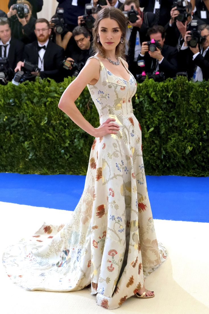 BEE SHAFFER in an ivory watercolor Alexander McQueen gown with patchwork print, plus a wreath necklace and drop earrings.