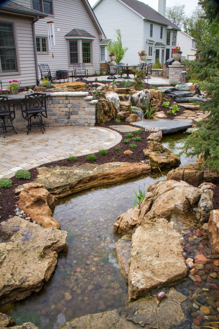 Stepping stones descend from the patio toward the pond, inviting visitors to explore the twists and turns of the stream and waterfalls.