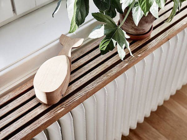 Beautiful wooden shelf over radiator.  A delightful Swedish home with dark wood features