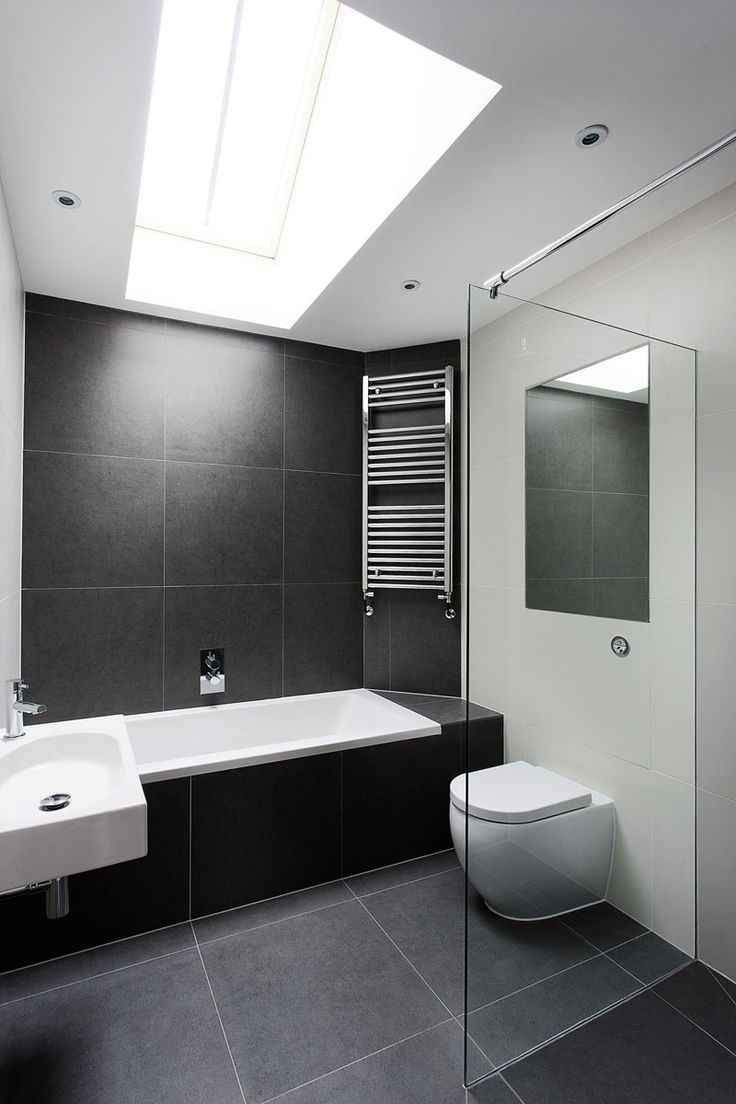 Bathroom Tile Idea - Use Large Tiles On The Floor And Walls (18 Pictures) | The large black stone tiles in this bathroom help to create a simple black and white color scheme, and the light from the skylight makes the bathroom feel taller and more open.