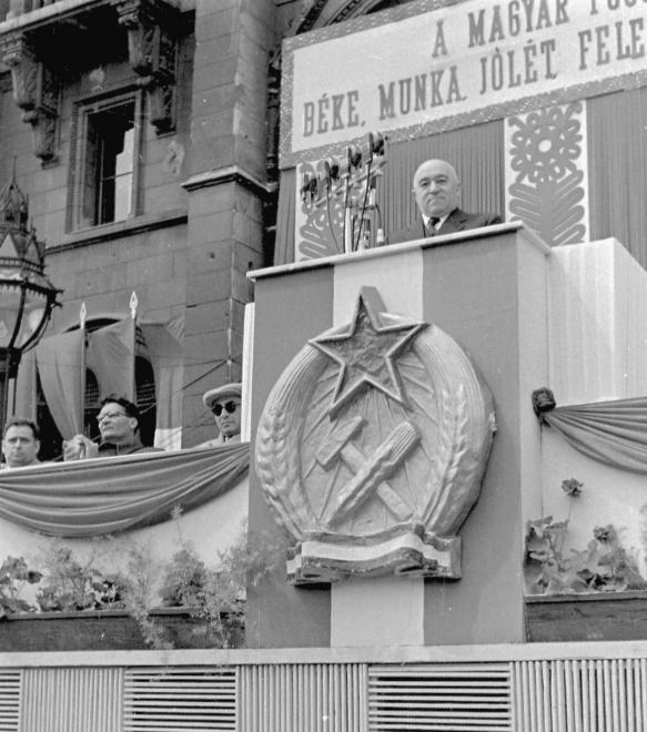 Kossuth Lajos tér, választási nagygyűlés, a Parlament főbejárata elé épített emelvény. Rákosi Mátyás beszél. Sötét szemüvegben Gerő Ernő, mellette Erdei Ferenc, tovább balra Hidas István.