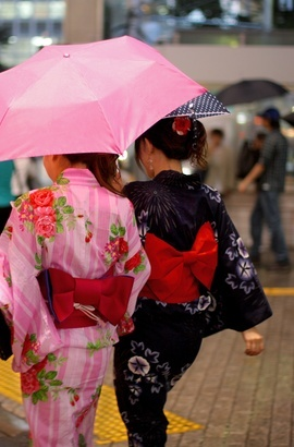 Japanese girls in traditional dress walking though the streets of Tokyo.