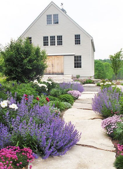Give a straight walkway graceful curves by planting perennials that gently tiptoe onto the surface. Here, catmint sprawls at regular intervals to create a sense of rhythm and repetition. Landscape by Ann Kearsley Design