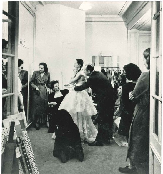 Christian Dior conducting a fitting in his atelier, 1947