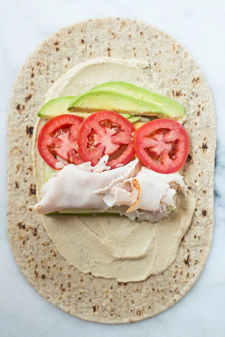 Avocado turkey hummus wrap laid out and ready to roll up