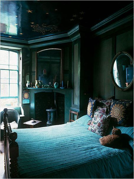Peaceful vintage bedroom with casement windows, corner fireplace, custom painted ceiling, hardwood furniture, and shades of blue.