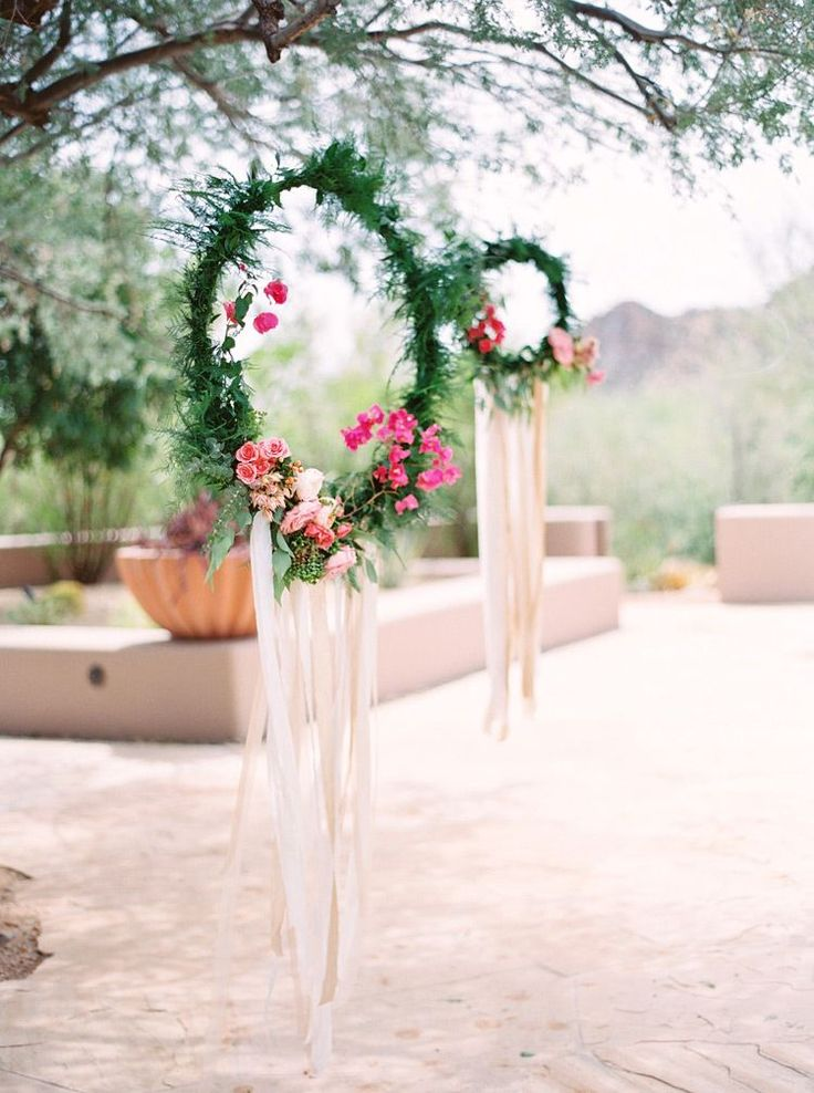 Wreaths of greenery and flowers with fluttering silk ribbons for a dreamcatcher look. Outdoor wedding  - Melissa Jill Photography