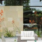 Behind the resin screen is the property's centerpiece: an entry garden that Trainor recast as an outdoor living room. Sparta stacking chairs, a deep-wicker Baia sofa, and matching Baia armchairs, all by Mamagreen, are arranged around a custom concrete fire pit. Orange kangaroo paws lean in from the sides, creating a sense of privacy without sacrificing views. It's a welcoming space that serves as a casual gathering spot when the weather cooperates.   Photo by Daniel Hennessy.