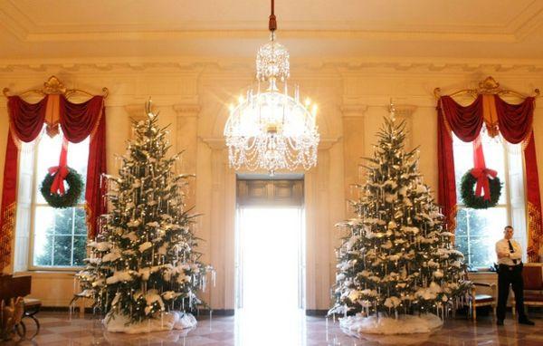 deux sapins de Noël et leur décoration imitation de neige et chandelles de glace