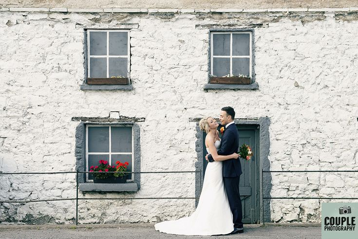 The newlyweds share a kiss outside the cute white washed ruin near their church. Weddings at Durrow Castle photographed by Couple Photography.