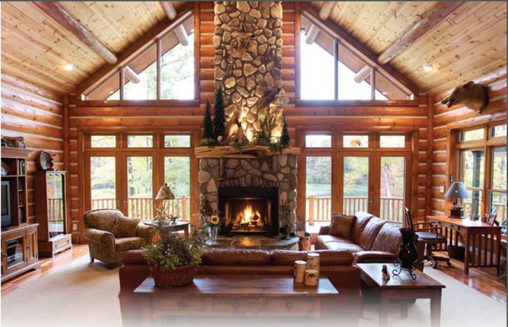 custom stone fireplace in the center of the great room in this hybrid log home
