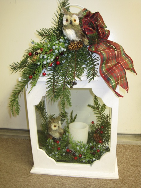 White holiday lantern with owls, greens and LED candle. From the Backyard Guest Theme at Your Christmas Shop at Stauffers of Kissel Hill Garden Centers. (http://www.skh.com/home-garden/departments-2/the-christmas-shop/)