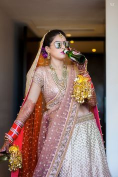 Indian Wedding Photography - Chilled Out Bride Wearing a Peach and Copper Lehenga with Orange Net Dupatta, Bride Drinking Beer | WedMeGood  #wedmegood #lehenga #beer