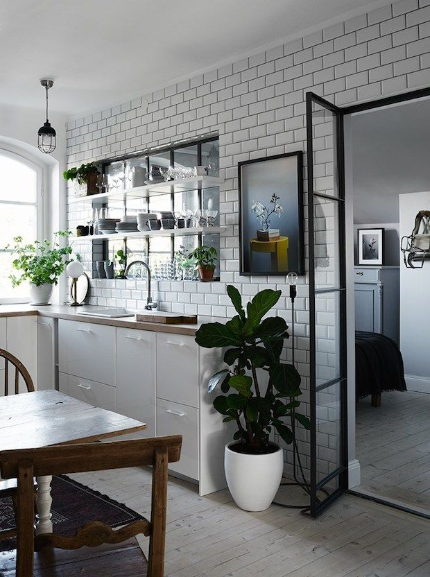 Kitvhen with subway tiles and shelves across the window in an elegant Stockholm pad Styling Anna Mårselius. Photography Kristofer Johnsson