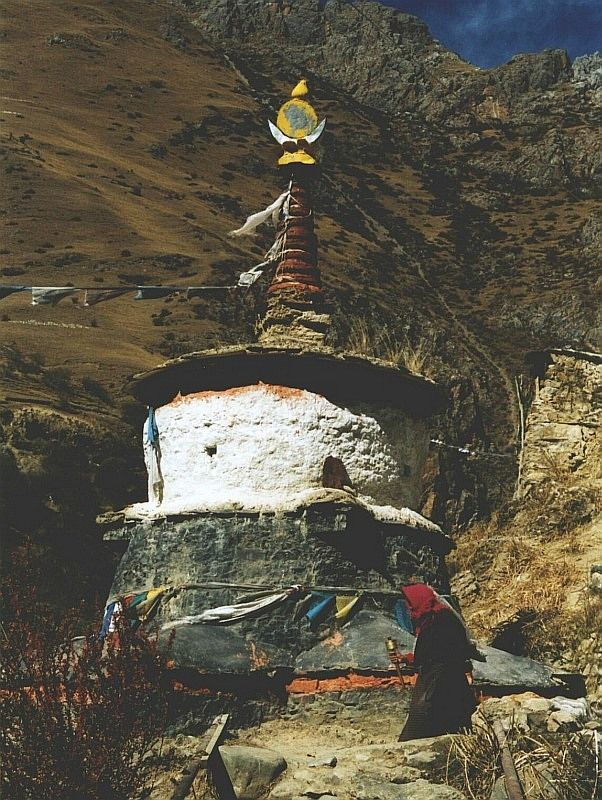 Stupa in the middle of nowhere - in Tibet a remote nunnery near to Nam-tso lake. There are hot springs nearby surrounded by the mountains. The nun is going around the Buddhist stupa with her praying wheel
