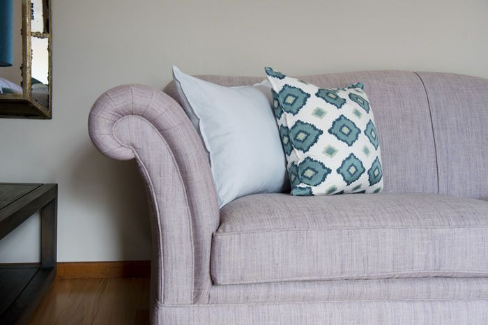 The mix of cushions in cool colours on the textured warm lavender sofa fabric gives this classic style a fresh feel.