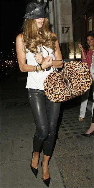 Elle Macpherson w/cropped black leather pants & fierce leopard-print bag...