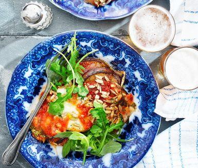 En inspirerande och fantastisk god vegetarisk rätt där milda aubergineskivor, tillsammans med smakrik tomatsås, riven mozzarellaost och gyllene solroskärnor, ugnssteks och serveras med nykokt pasta och rivig rucolasallad. Ett recept som båda mättar och värmer i höstmörkret!