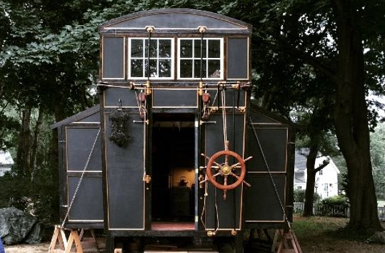 Tiny House built from movie set leftovers and other reclaimed materiels has an interesting exterior, slide-outs and expanding-up roof