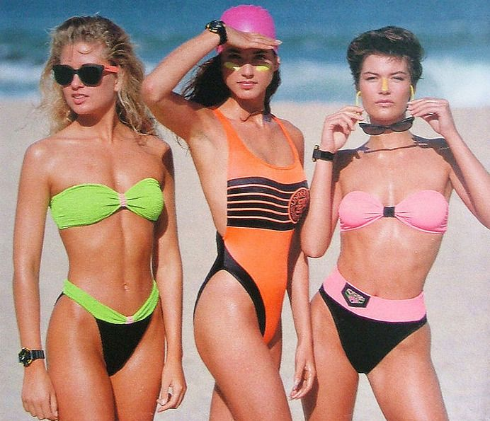 80s inspired swimwear shoot with neon colours, high rise bikini bottoms, wayferer style shades and a bright pink swimming cap. Why not?