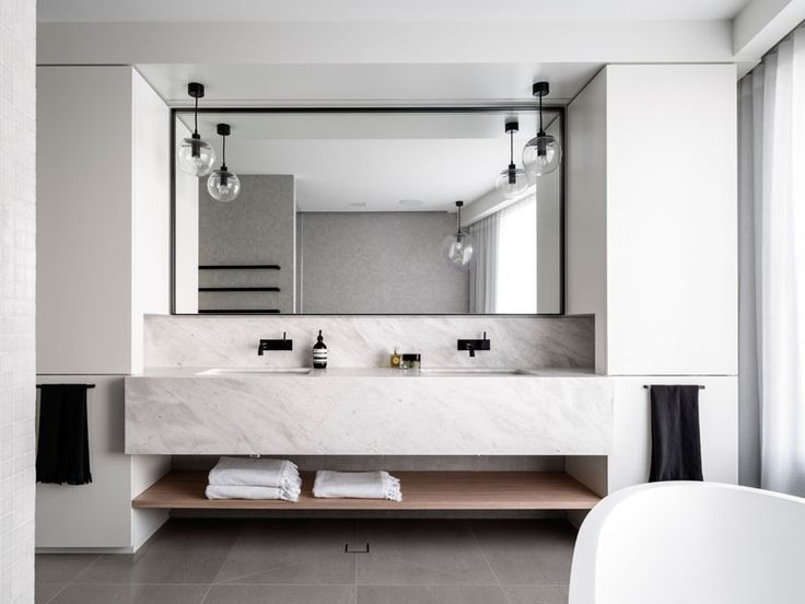 Bathroom Design Idea - An Open Shelf Below The Countertop (17 Pictures) | The little bit of wood included in this bathroom in the form of an under the sink shelf adds just enough warmth to the space to keep it from feeling cold and uninviting.