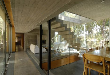One of the most prominent features of the house is a concrete staircase that cuts through its centre, connecting the rooms on the main floor with an entrance on the storey below and a terrace on the rooftop.