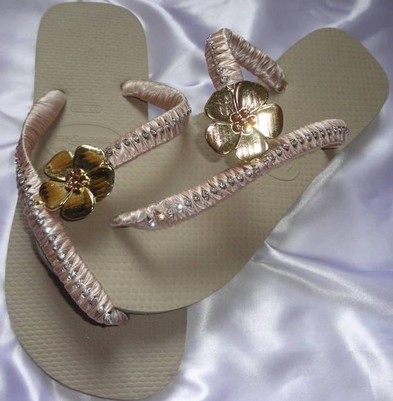 Chinelo Havaiana Top Bege, com corte lateral, flor de metal dourada com miolo de strass e com fio de strass em toda a correia. R$ 50,00