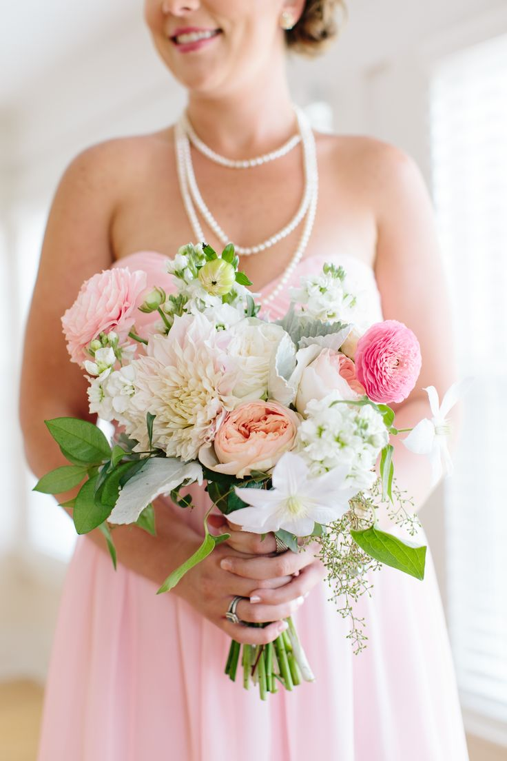 bridesmaid in soft pink dress carries her bouquet of cafe au lait dahlia, peach juliette garden rose, pink ranunculus, white rose, white stock, white clematis, dusty miller, seeded eucalyptus and lemon leaf.