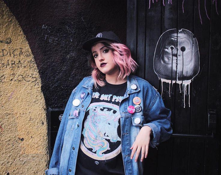 Look com camiseta de unicórnio da Insomnie, jaqueta jeans com botons e  boné preto