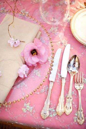 Very elegant clear beaded plates a top a very pretty pink table cloth.