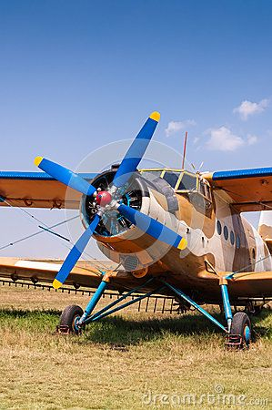 Agricultural aircraft parked on grass, copy space at top on blue sky.