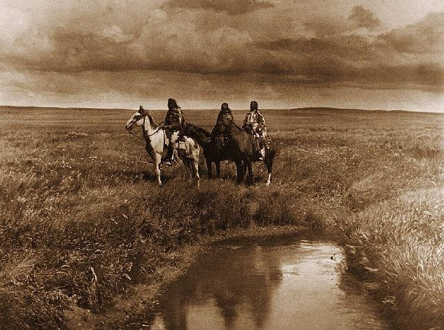 The Three Chiefs - Piegan  1900 -  photogravure   Three proud old leaders of their people. A picture of the primal upland prairies with thir waving grass and limpid streams. A glimpse of the life and conditions on the verge of extinction. Their territory, yielding great quantities of furs hides for barter, was animportant one to traders. Those great rival corporations, the Hudson's Bay Company and the North West Company, established posts in their midst.