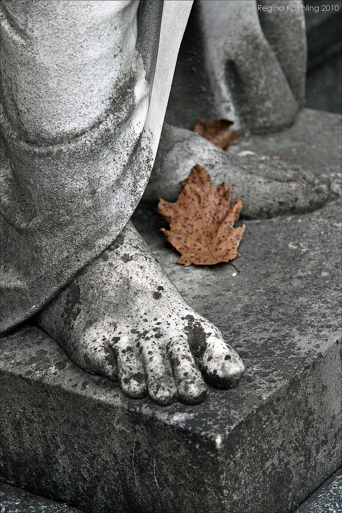 Autumn leaf on cemetery statue in Pragfriedhof, Stuttgart, Germany.