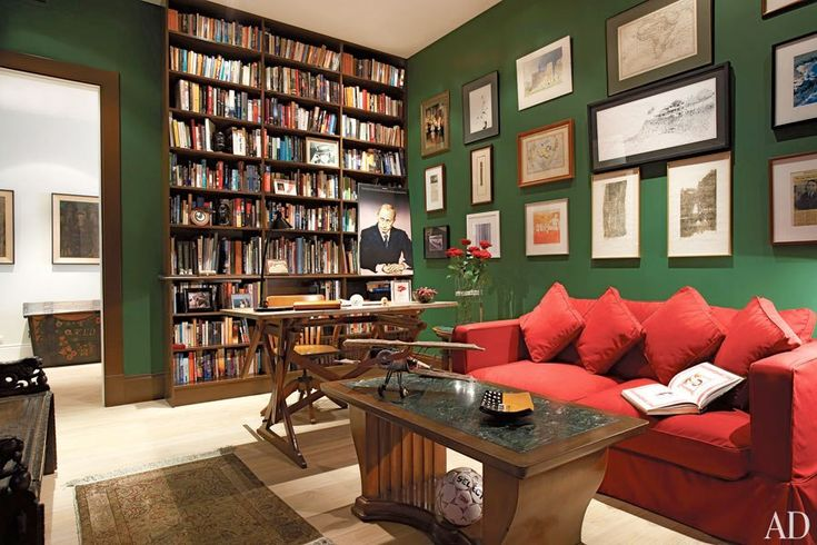 """British banker Stuart Lawson enlisted designer Jaime Hunt to streamline his Moscow apartment. A palette of creams was used throughout the apartment, except in the library, which is painted in what Lawson calls a """"dark British-club green."""" A 19th-century architect's desk, an Art Deco cocktail table, and a sofa slipcovered in red cotton furnish the room."""