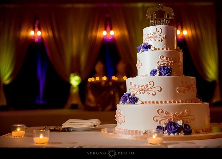 A perfectly detailed ivory wedding cake with purple flowers and salmon colored designs from Oak Mill Bakery