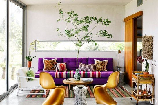 In the living room, gold Verner Panton chairs join a purple sofa accented with a striped Peruvian textile and pillows made of African fabrics; a rope-framed mirror by Christian Astuguevieille is mounted above a vintage American bamboo bar cart.